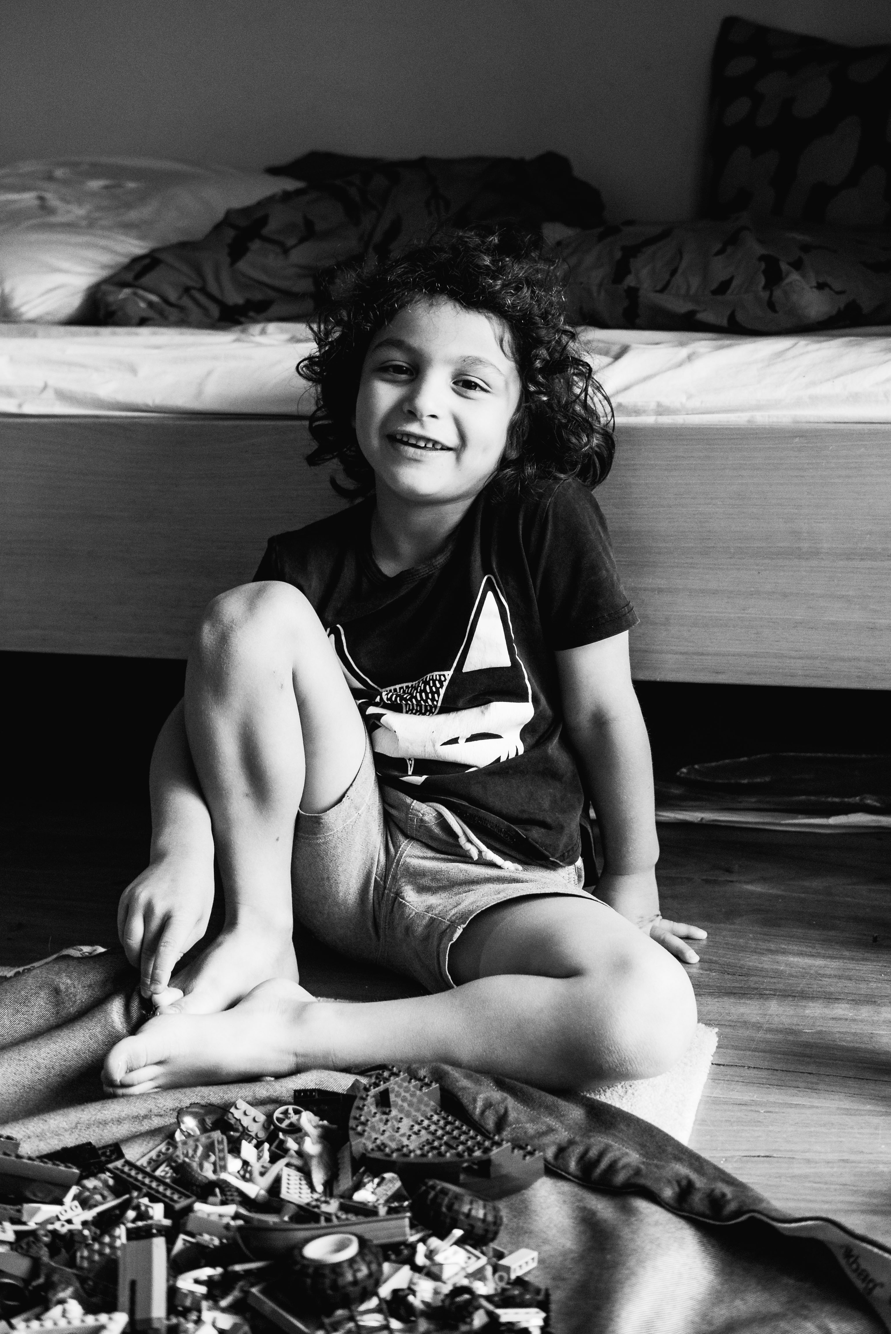 in-home session photograph of a boy smiling and sitting by his bed in Carlton North, Melbourne, Australia