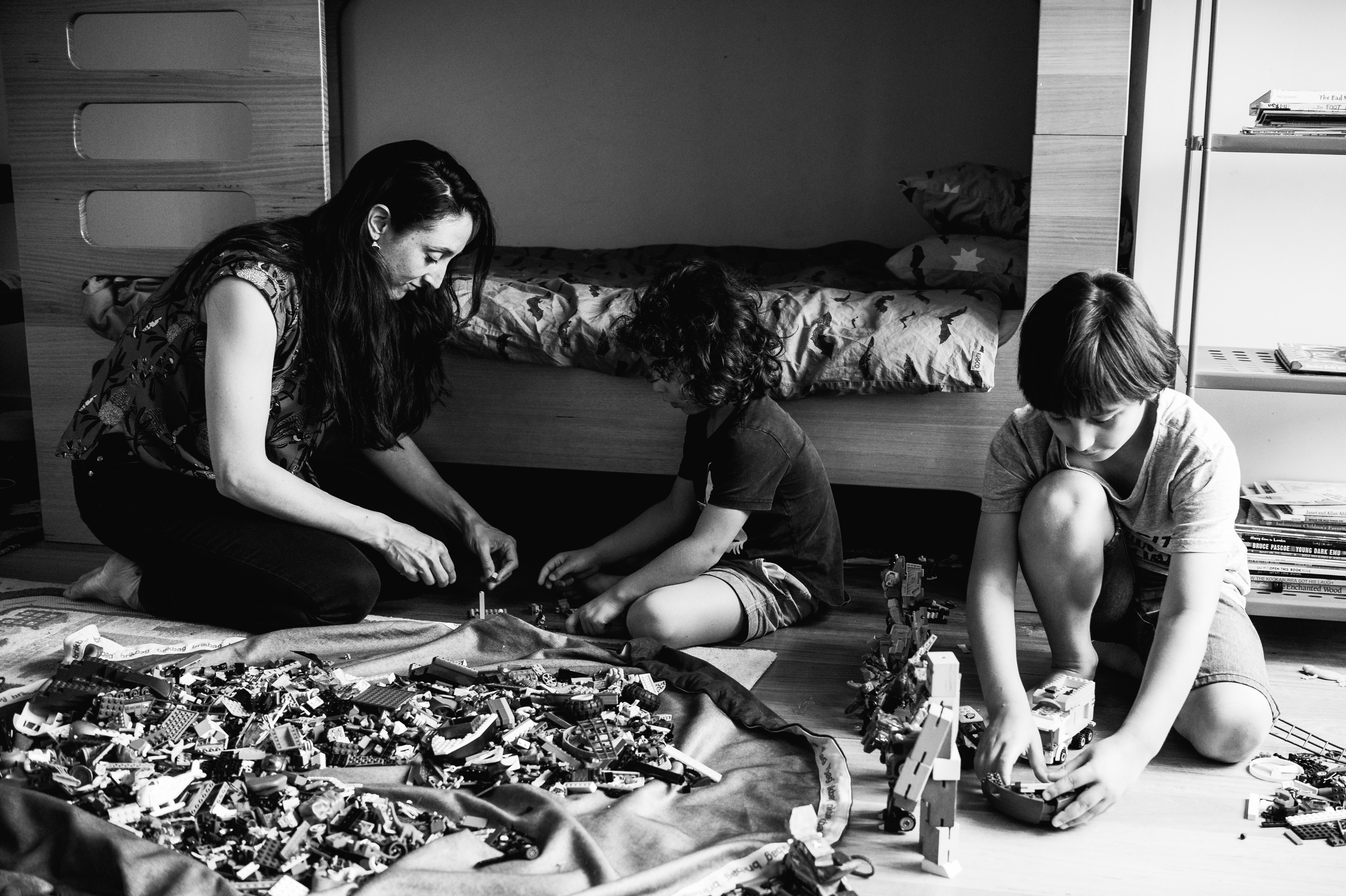in-home session photograph of mother and her boys creating and building with Lego in their bedroom in Carlton North, Melbourne, Australia