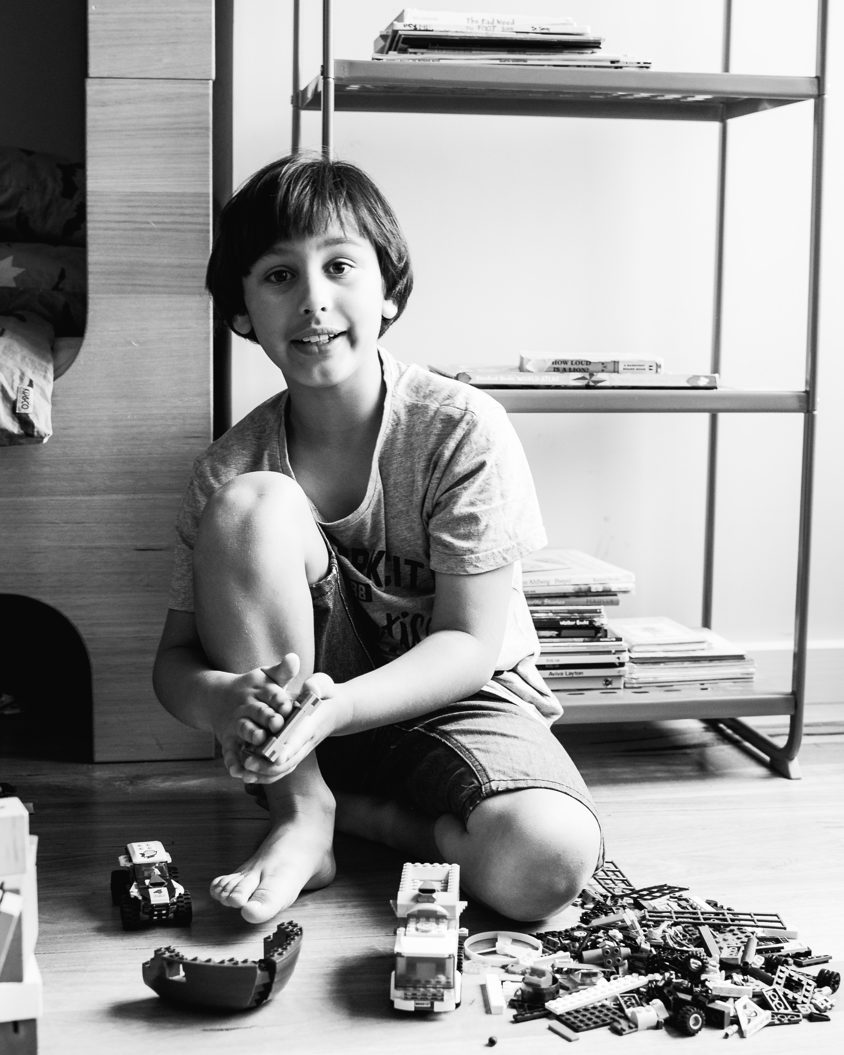 in-home session photograph of a boy talking while creating and building with Lego in his bedroom in Carlton North, Melbourne, Australia