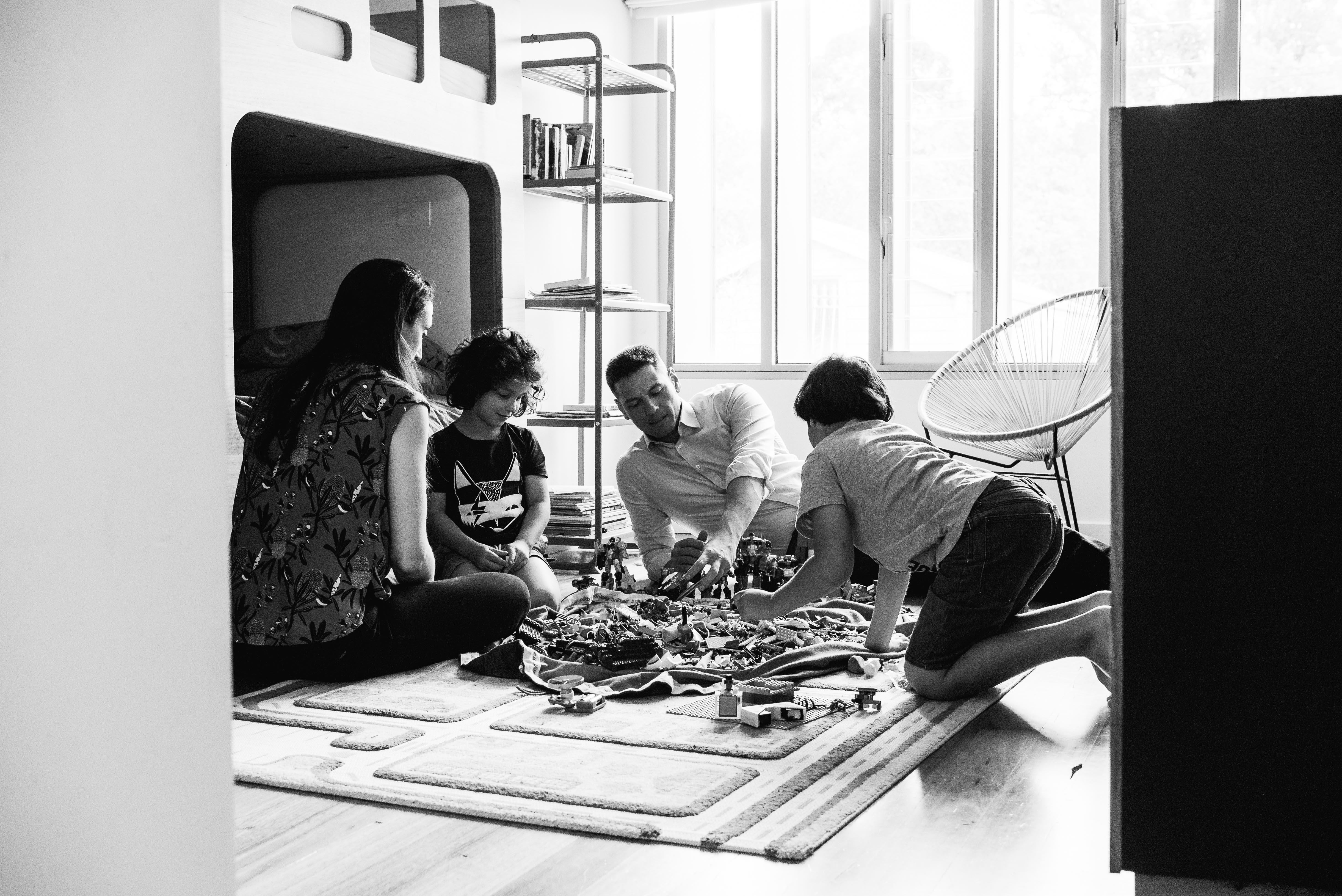 in-home session photograph of parents and their children creating and building with Lego in their bedroom in Carlton North, Melbourne, Australia