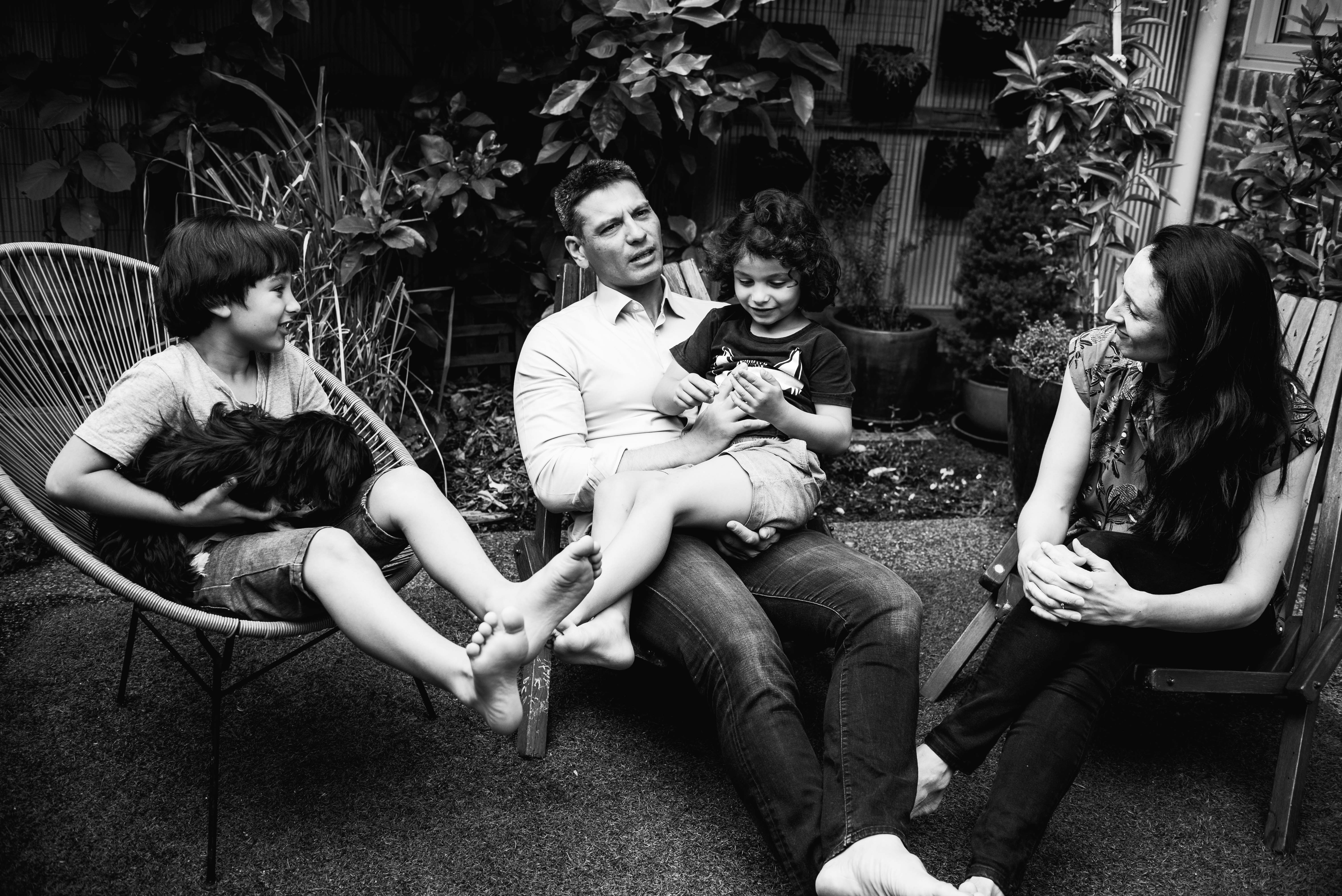 photograph of a family sitting in their backyard, talking in Carlton North, Melbourne, Australia