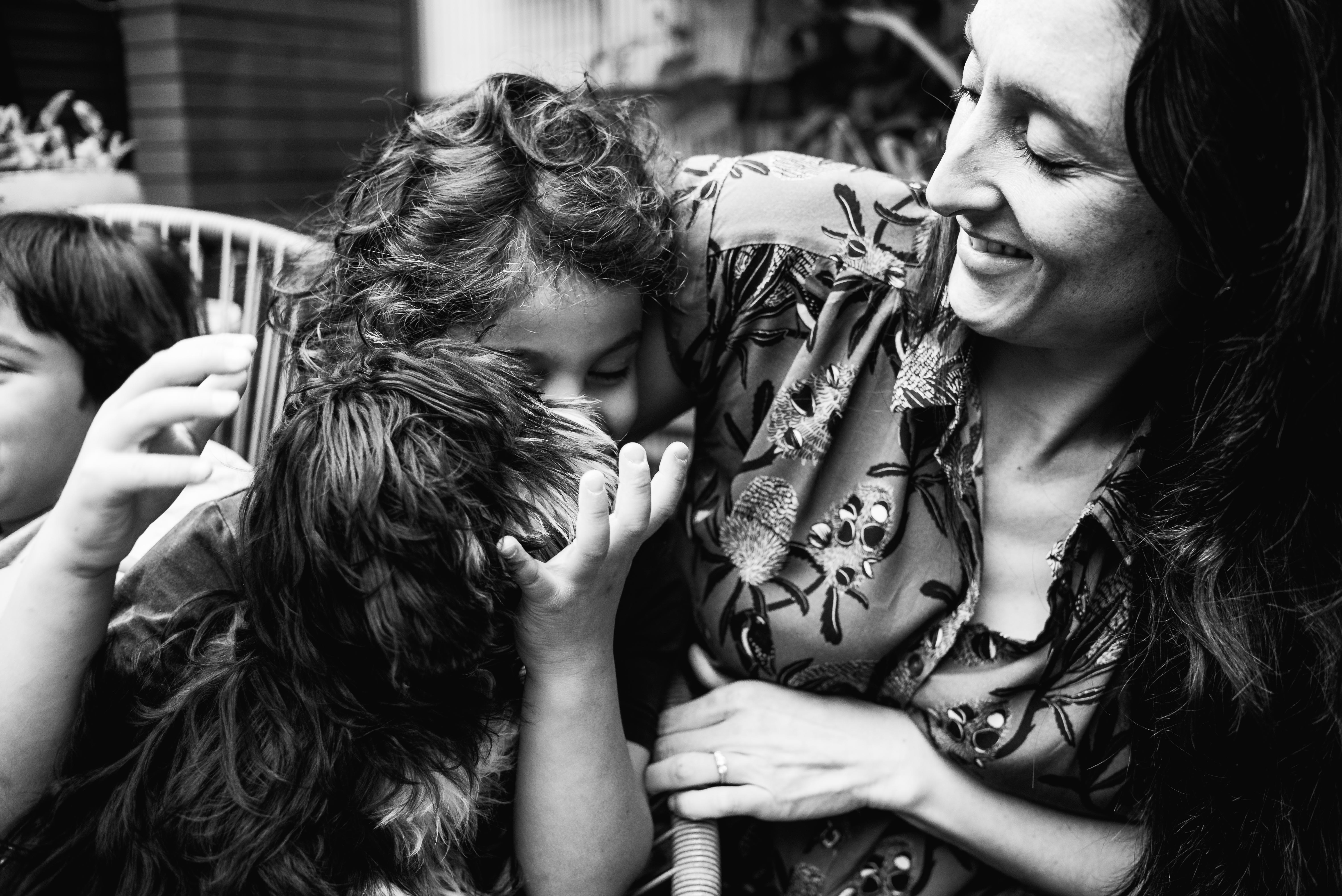 photograph of a boy holding his pet dog and cuddling his mother in Carlton North, Melbourne, Australia