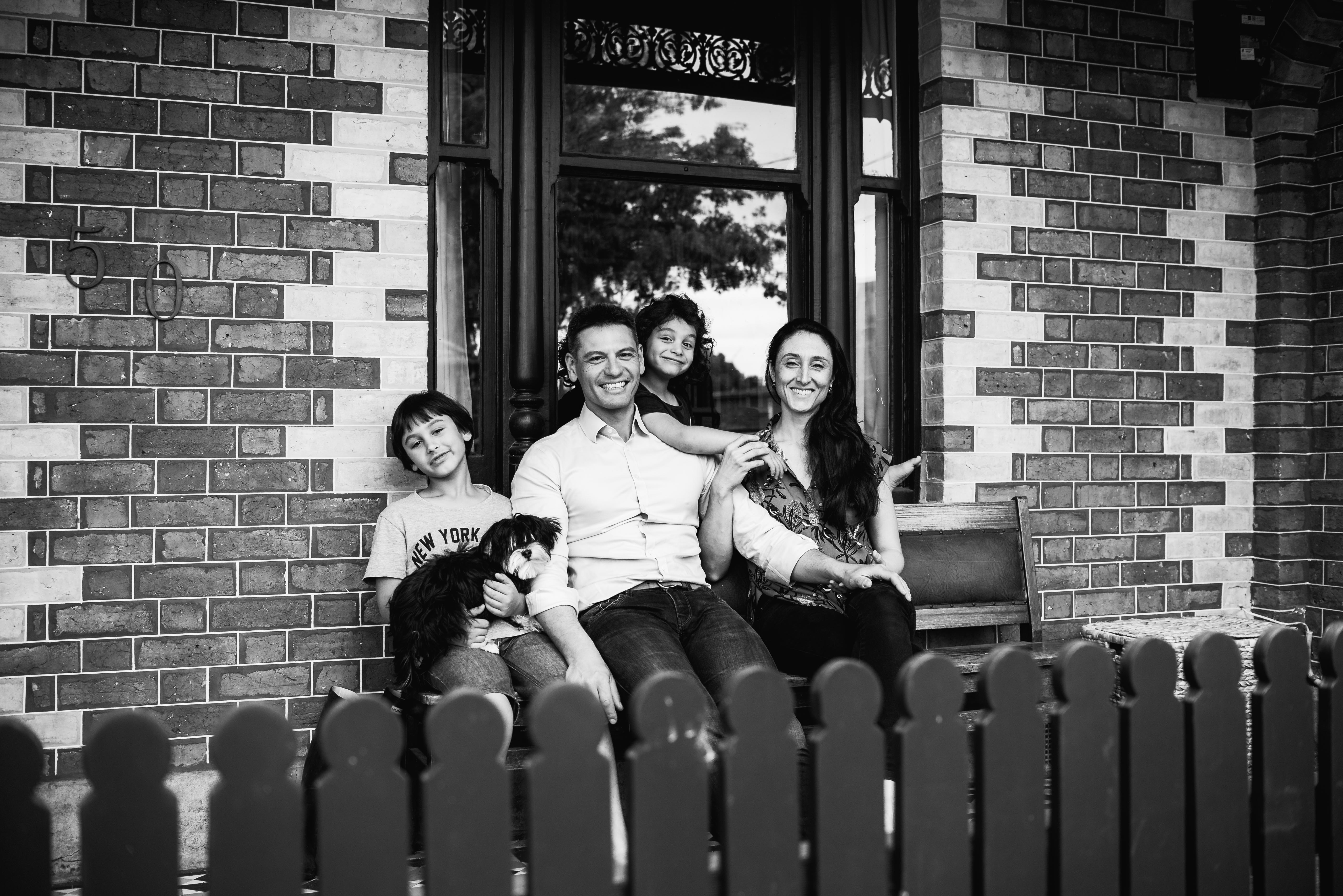 in-home session photograph of a family sitting at the front of their home in Carlton North, Melbourne, Australia