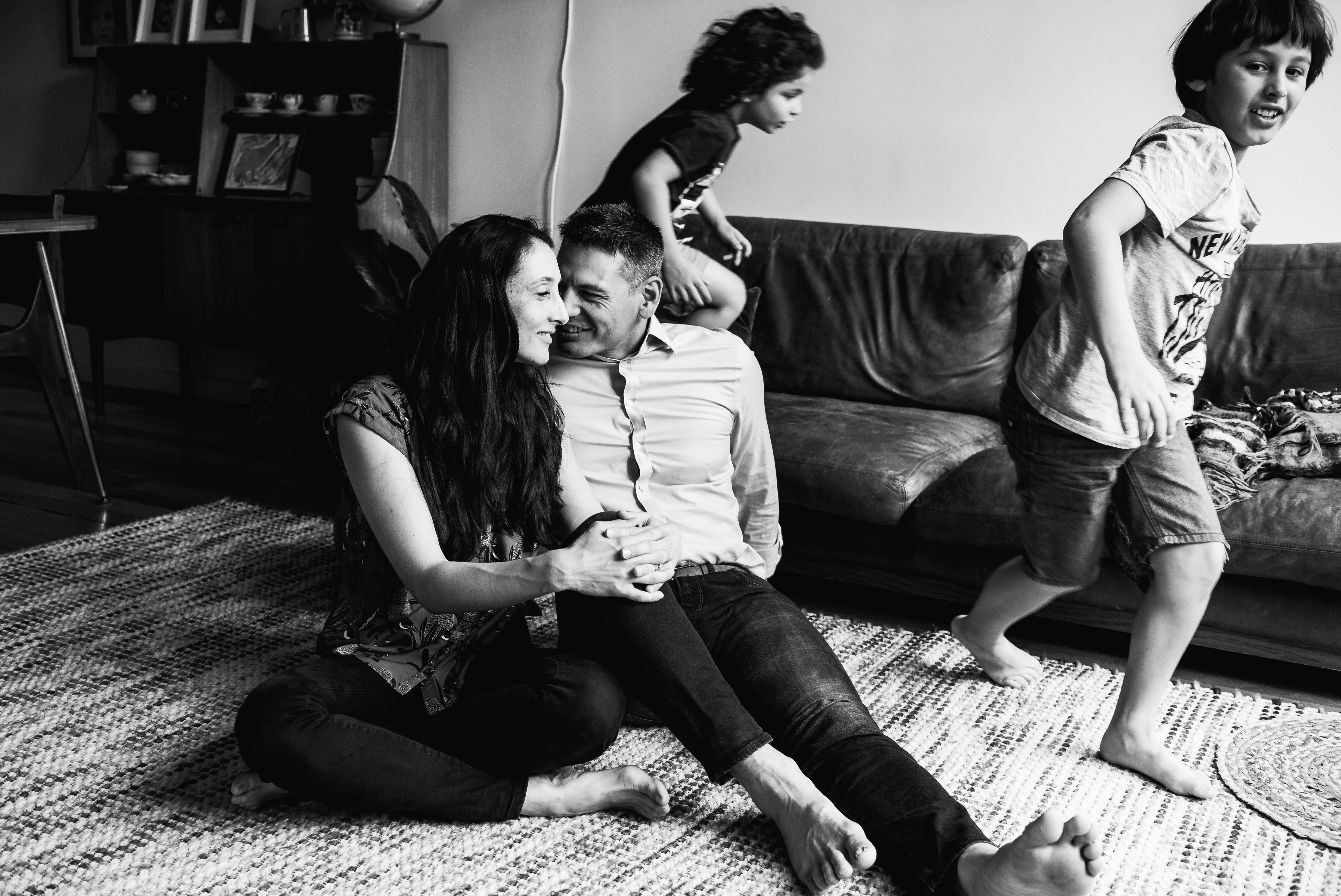 in-home session photograph of parents talking and laughing as boys run around in circles in Carlton North, Melbourne, Australia