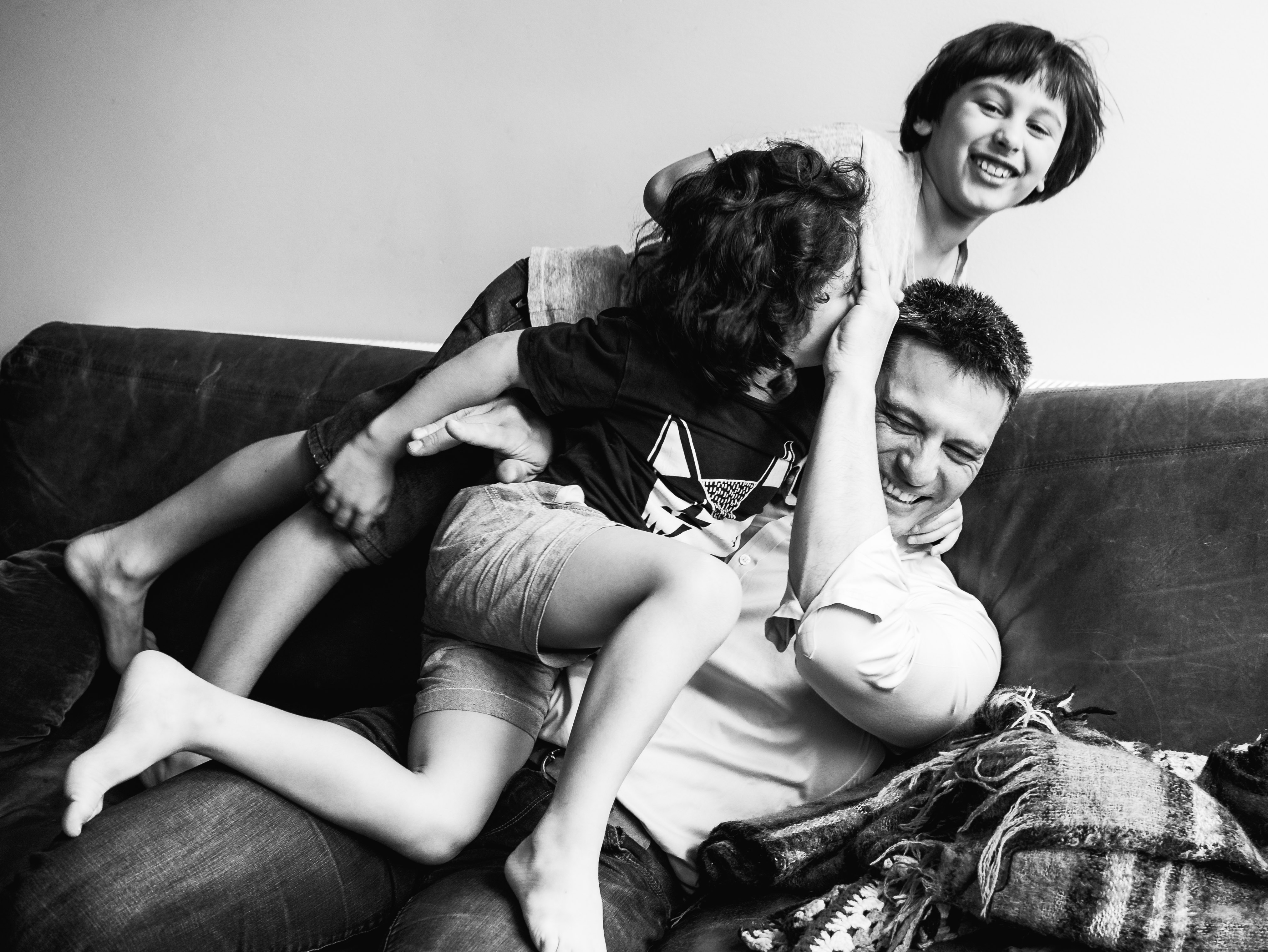 in-home session photograph of boys wrestling their father on a couch/sofa in Carlton North, Melbourne, Australia