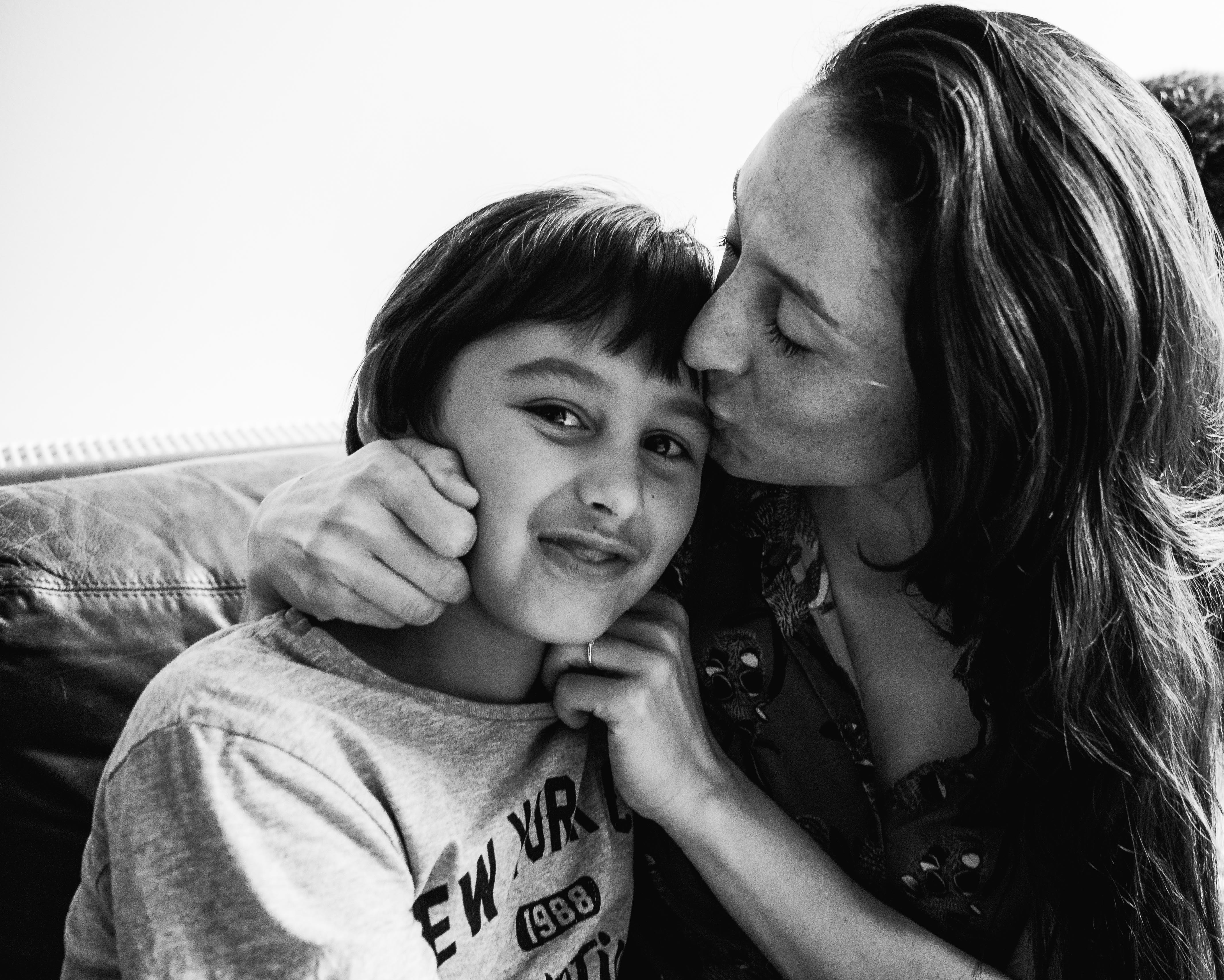 in-home session photograph of mother kissing and cuddling her son in Carlton North, Melbourne, Australia