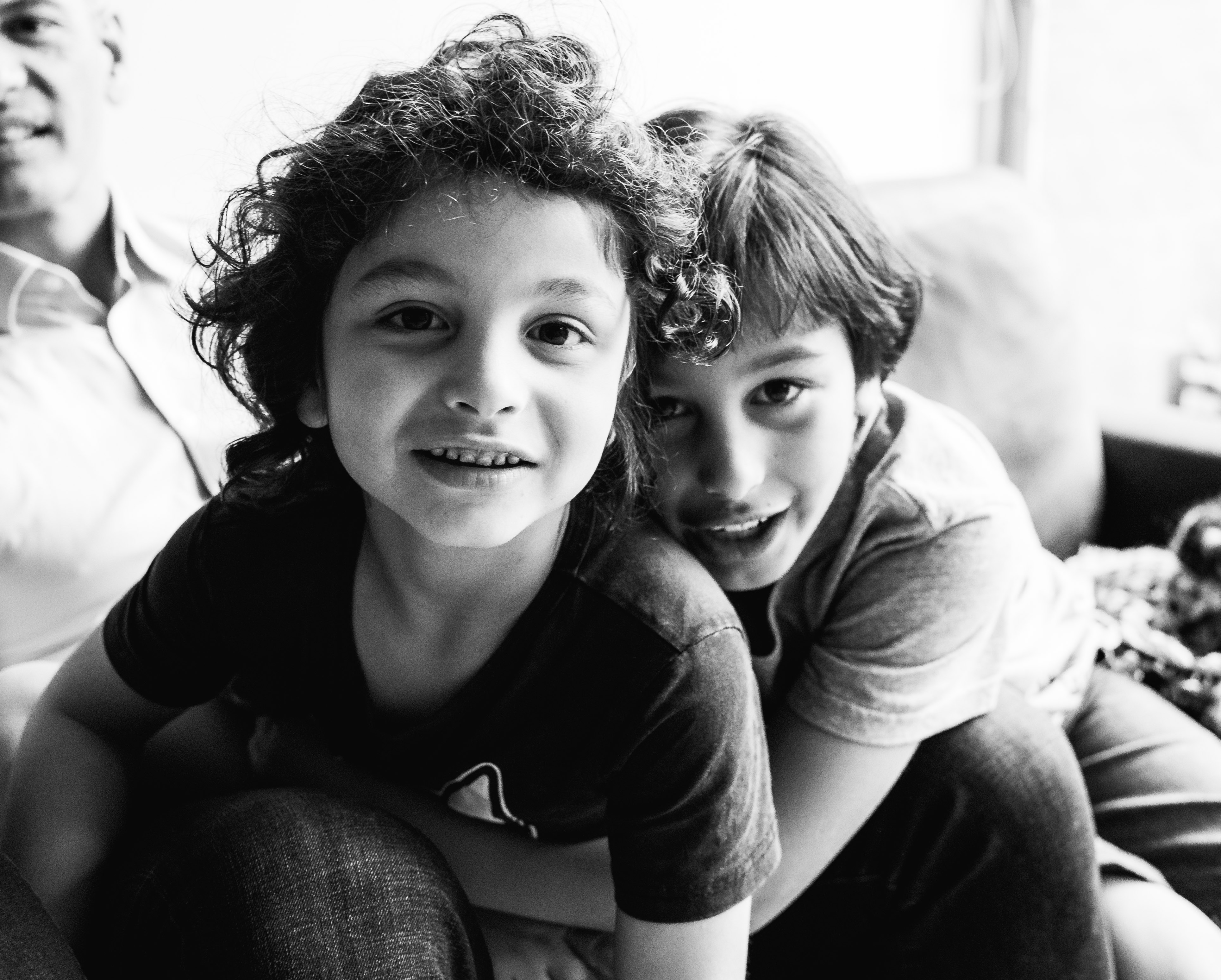 in-home session photograph of brothers cuddling and looking straight into camera lens in Carlton North, Melbourne, Australia