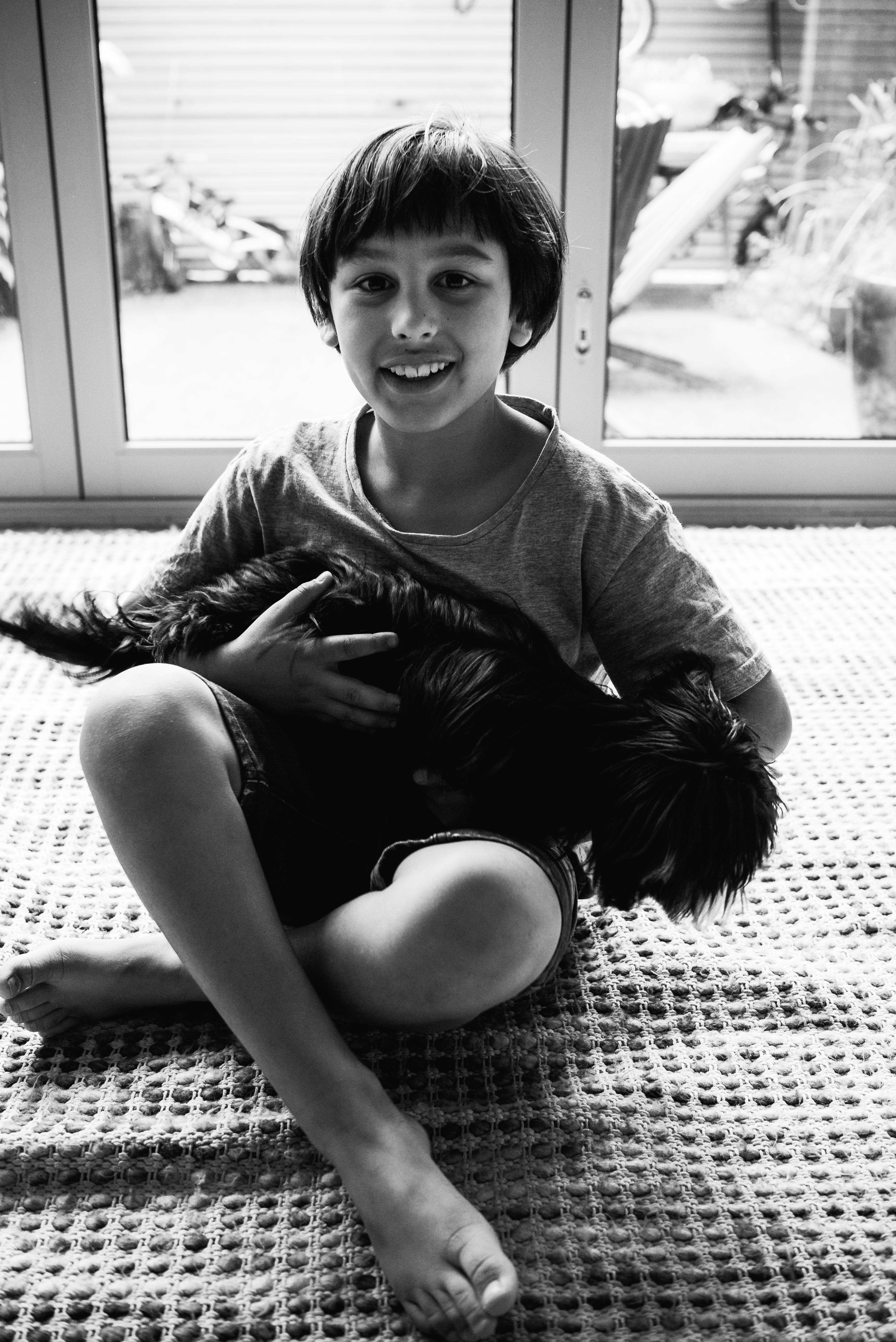 in-home session photograph of a boy and his cute dog cuddling in Carlton North, Melbourne, Australia